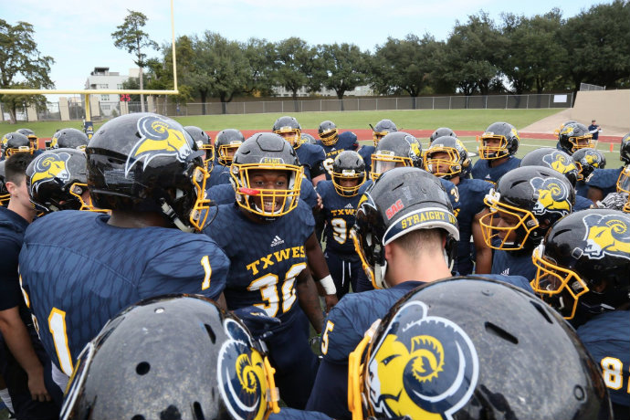 Photo of TXWES football team in a huddle before their homecoming weekend game.