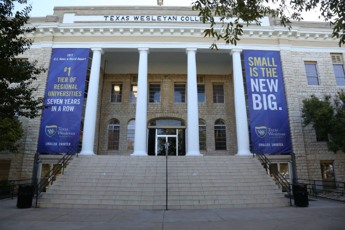 "Outside view of Oneal-Sells Administration building at Texas Wesleyan. Displayed on the building are banners saying ""Small is the new big,"" and ""#1 tier of regional universities seven year in a row from U.S. News & World Report."""