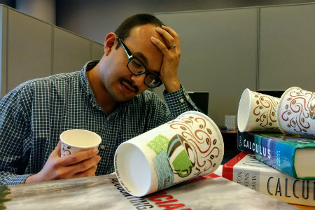 stressed student studying with books and coffee cups
