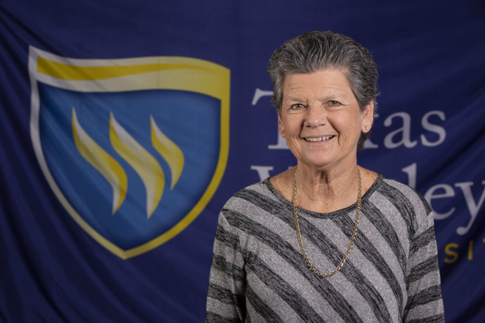Photo of a man in a gray shirt in front of a Texas Wesleyan logo backdrop