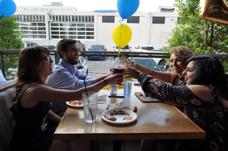 Texas Wesleyan students toast at graduate celebration.