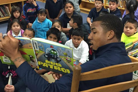 Texas Wesleyan basketball player reading to kids