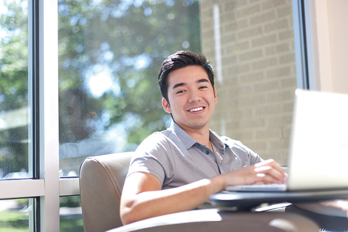 Photo of smiling student studying on a laptop.