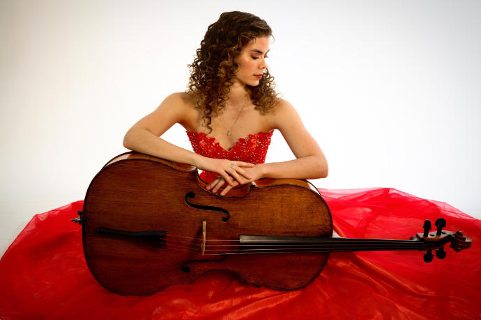 A photo of Katherine Audas, a young woman in a red dress holding a cello lengthwise across her lap