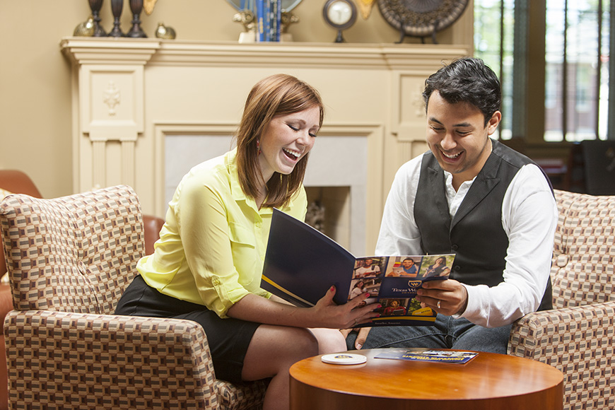 Admissions & Aid - Meet With a Counselor - Freshman Counselor - Female counselor sitting with a student going through a Texas Wesleyan book