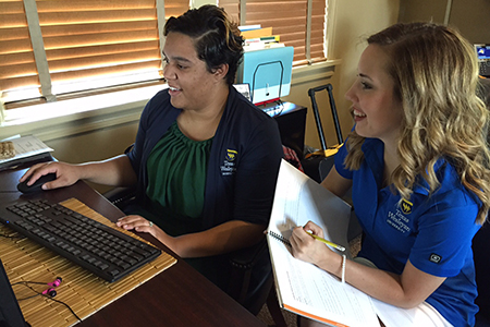 Melondy Doddy (left), admissions counselor and community outreach coordinator, reviews a monthly progress report with Nicole Gillihan, G-Force mentor and junior education major.