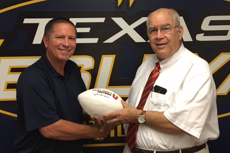 Head Football Coach Joe Prud'homme and Dr. Jon Crook with football signed by John Gagliardi