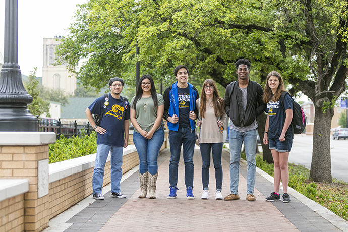 Photo of students walking together in a group on the Texas Wesleyan campus.