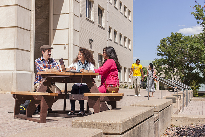 Photo of students sitting around a picnic table in front of the West Library.